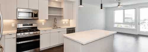 Interior of AMLI Park Broadway apartment kitchen with quartz countertops, white cabinetry facing living room and large window