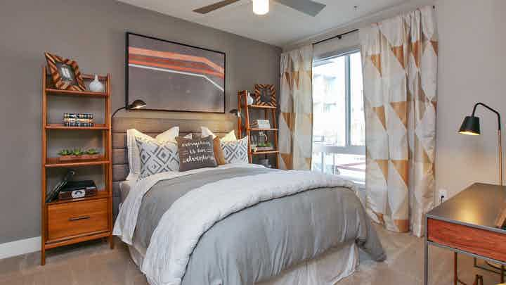 Interior view of AMLI Uptown Orange apartment bedroom with full bed, night stands and large window overlooking pool courtyard