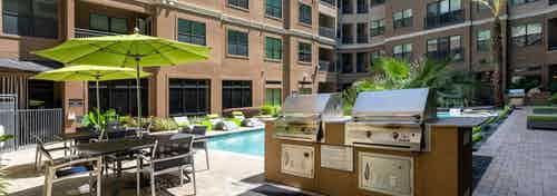 Daytime view of poolside gas grill station and tables with chairs and green umbrellas at AMLI Uptown apartments