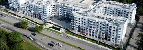 Aerial view of the exterior of AMLI Midtown Plantation apartment community with main street and modern architecture
