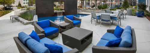 Daytime exterior view of sitting area in AMLI Piedmont Heights courtyard showcasing small and cozy couches with blue cushions