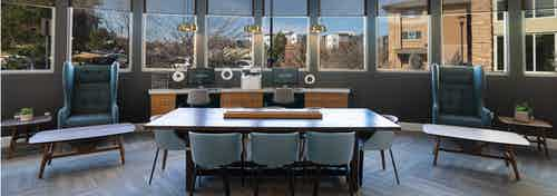 Business center at AMLI Inverness apartments with conference table and chairs and coffee tables as well as several windows