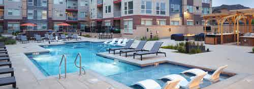 Evening view at AMLI Littleton Village pool with lounge seating and fire pit with TV and grill and apartment building in rear