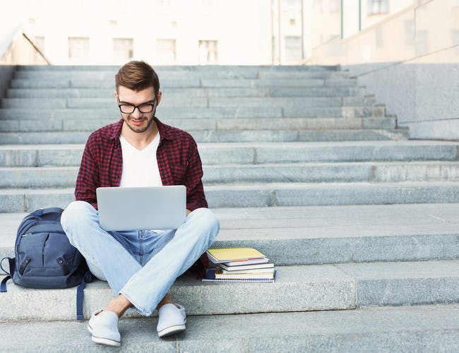 Guy studying with laptop and books on strps