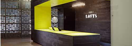 The Polk lobby at AMLI Lofts which has a deep brown textured accent wall and matching desk that has a vibrant yellow lining
