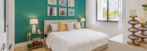AMLI Park West apartment bedroom with queen bed on teal wall with two gold nightstands and white lamps and side window