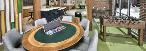 AMLI Decatur clubroom with a poker table and foosball with an arcade game as well as billiards and a serving kitchen