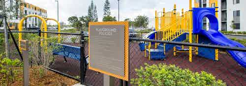 Outdoor bright yellow and blue children's playground at AMLI 8800 featuring stairs for climbing, slide and swing set