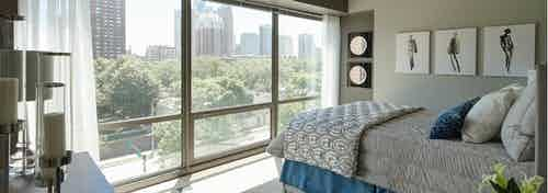 Neutral tone bedroom at AMLI 900 in which the bed faces a massive window with a view of city buildings and vibrant foliage