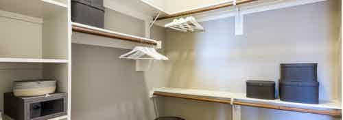 Interior view of walk in closet at AMLI on Riverside with built in shelving of different heights and white clothing hangers