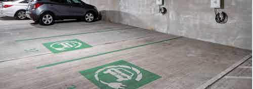 Electric car charging station in the parking garage at AMLI Buckhead with grey and white cars parked in the background