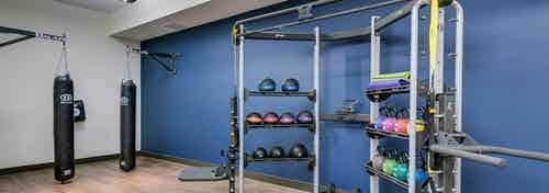 Interior view of the fitness center at AMLI Cherry Creek apartments with heavy punching bags and several medicine balls