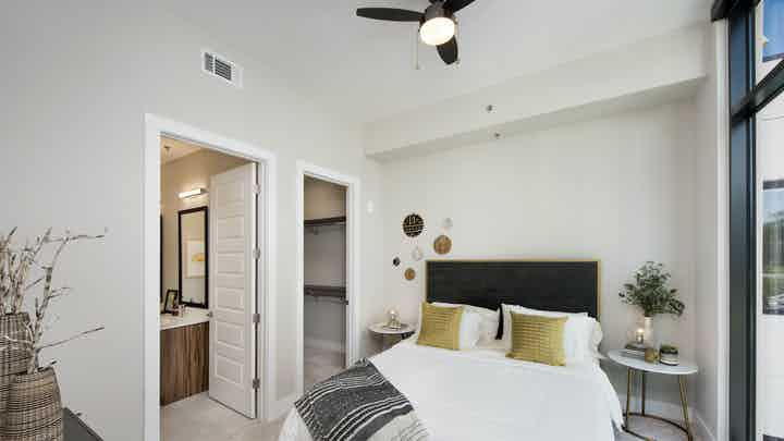 AMLI Lenox bedroom with floor to ceiling window and a bed with a white comforter and bedside nightstands and walk in closet