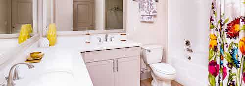 A bathroom at AMLI Park Avenue apartments with white counter tops and two sinks and mirrors with a colorful shower curtain