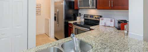 Interior view of AMLI Toscana Place apartment kitchen with double stainless sink and granite counters and wood cabinetry