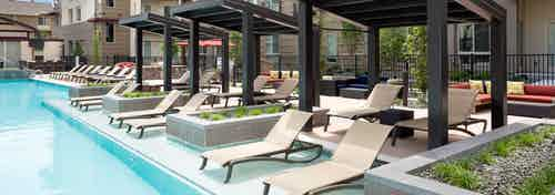 Exterior view of the pool at AMLI Cherry Creek apartments featuring a poolside cabanas with lounge chairs and planter boxes