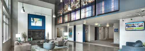Interior of the spacious lobby with seating are and elaborate fireplace view of mailboxes and Seattle skyline mural