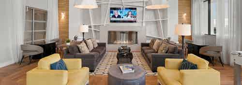 Interior view of AMLI 8800 resident lounge with entertaining seating area, yellow accent armchairs, fireplace and TV on wall