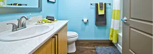 Interior view of an AMLI Mark24 apartment bathroom with bright blue walls white quartz counter top light cabinets and shower bath combination