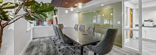 AMLI Bellevue Park conference room with wood paneled ceiling over large conference table surrounded by eight gray chairs