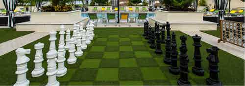 Game view of AMLI Dadeland Rooftop with life sized chess game and a view of the pool and lounge chairs