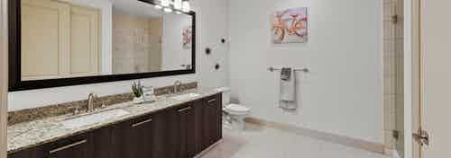 Interior view of AMLI 8800 apartment bathroom with double vanity, mirror, toilet and granite counters