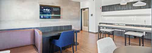 Interior view of AMLI Bellevue Park sky lounge with table and chairs and kitchen with hanging lights and TV near door