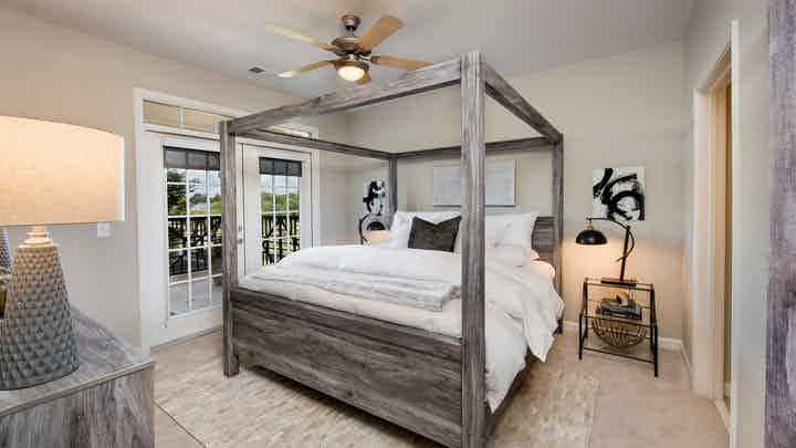 Bedroom at AMLI North Point with french doors leading outside and rustic styled decor with a canopy framed bed