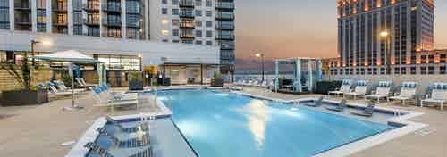 Dusk view of pool area at AMLI Lenox apartment building with lounge chairs and cabanas around the pool with building set back