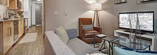 AMLI Mark24 apartment living room view with light floors and view of shot gun kitchen to the entrance of the apartment