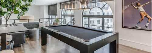 Second floor interior view of the AMLI Joya two story game room with billiards table and artwork of tennis player
