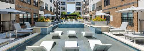 A sunlit shallow pool at AMLI Quadrangle apartments with lounge seating with shading umbrellas and flowers in metal planters