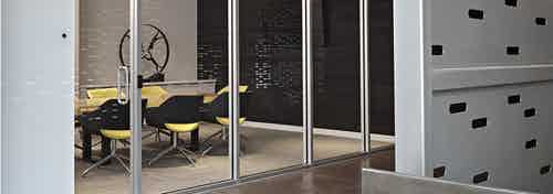 Conference room at AMLI Lofts with a clear glass wall and a conference table paired with bright yellow office chairs