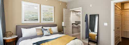 Interior of AMLI West Plano bedroom with tan walls and a white bed with a yellow throw blanket and a peek into walk in closet