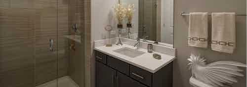 Bathroom at AMLI Lofts with taupe decor and a single vanity as well as a beige tiled shower with a clear glass door