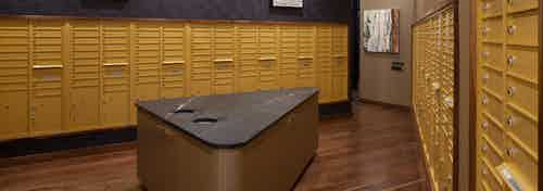 Mailroom at AMLI Riverfront Green apartments with all resident mail boxes and island table with trash receptacles