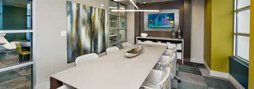 AMLI Buckhead conference room with a long white conference table with patterned chairs and square carpeting with blue shades