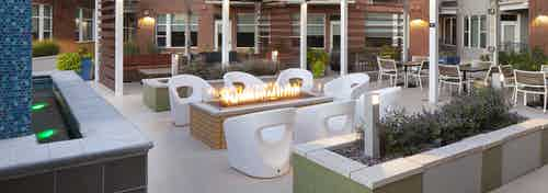 Night time view of rooftop area at AMLI Riverfront Green apartments with fire pit featured with chairs and planter boxes