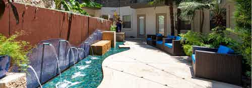Daytime view of AMLI 300 relaxing zen garden with blue fountains and reclining brown wicker chairs and blue pillows