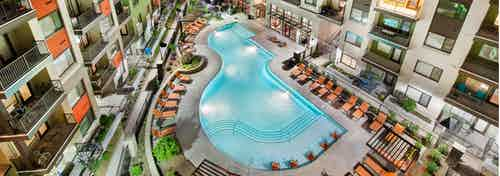 Aerial view of AMLI Ponce Park pool shaped like a teardrop with the apartment building and lounge chairs surrounding it