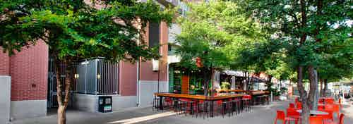 Exterior of retail shop on the first level of AMLI Downtown with orange outdoor barstools and tables with surrounding trees
