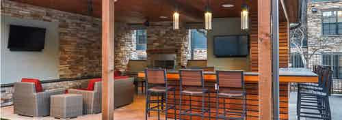 AMLI Covered Bridge outdoor pool cabanas with full outdoor kitchen, fireplace, lounge seating and televisions