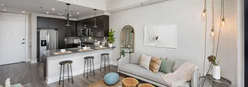 Interior of AMLI Lenox apartment with light sofa and hanging lights and three bar stools at an island overlooking the kitchen
