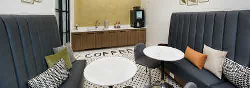 Interior of coffee bar featuring Starbucks coffee at AMLI Decatur apartments with cafe tables and booth seating