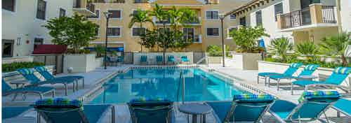 One of two swimming pools at AMLI Dadeland surrounded by lush palm trees, blue deck chairs and can be seen from the patios