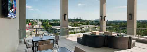 Daytime exterior view of AMLI Piedmont Heights sky deck with various seating areas overlooking Atlanta skyline