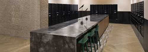 Mail room at AML Park Broadway apartment building with a long sleek quartz counter surrounded by black mailboxes