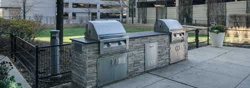 Stainless grilling station at AMLI 900 apartments with greenery and a view of two parking structures in the background