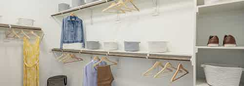 Interior of walk in closet at AMLI Addison with built in shelving of varying heights with wooden hangers for clothing