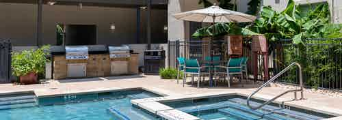 Exterior view of daytime AMLI 300 poolside gas-grills and dining area with teal chairs and an umbrella-shaded table